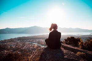 woman sitting in front of sunset